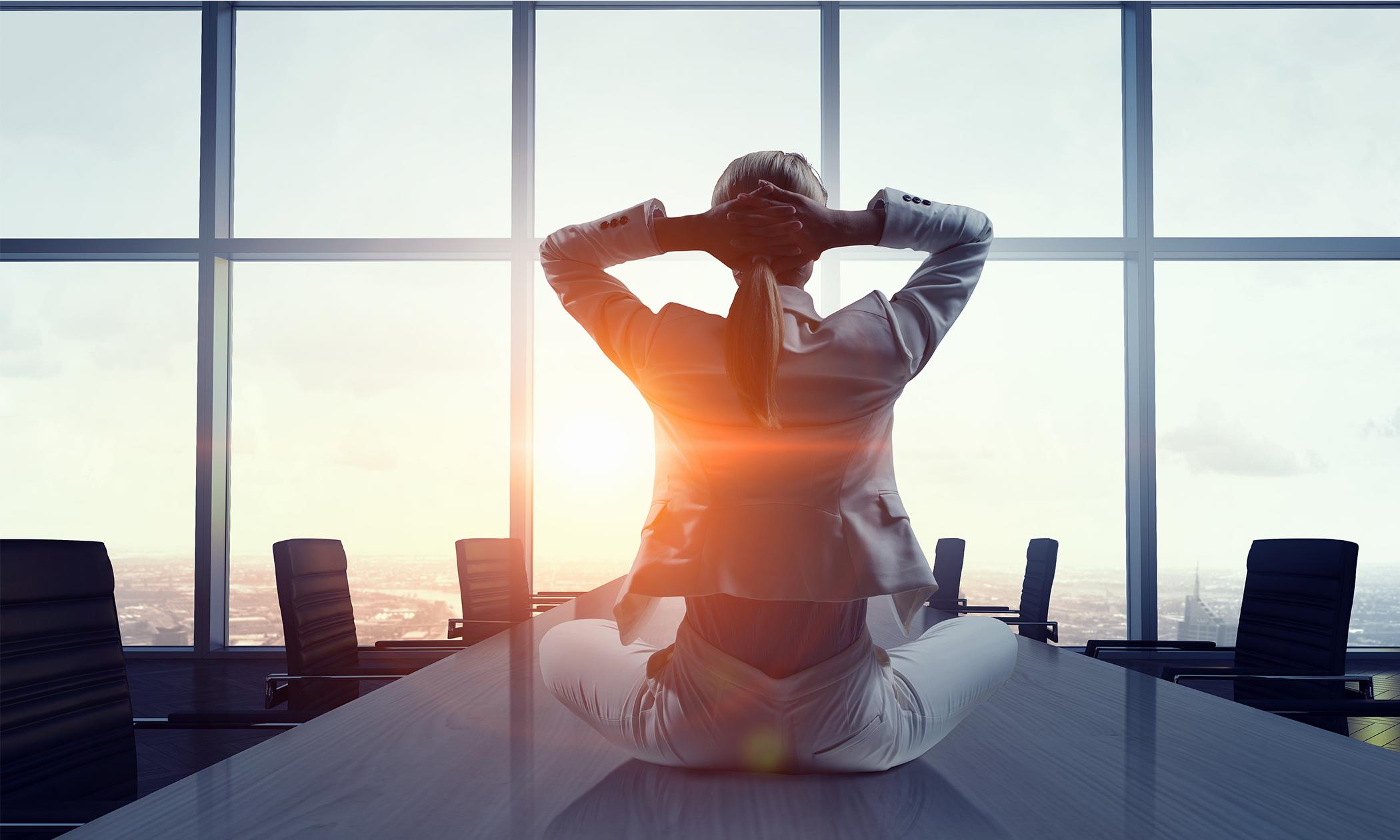 Meditierend auf einem Konferenztisch sitzen