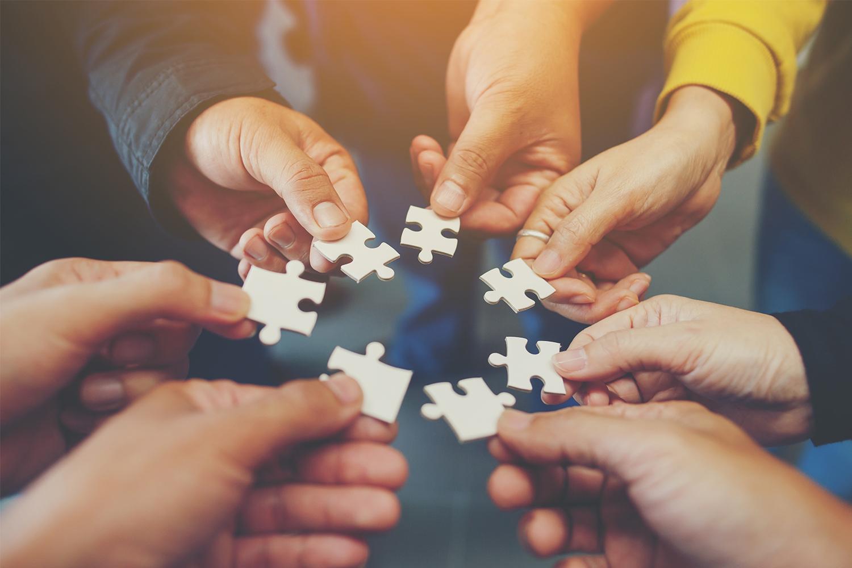 Menschen fügen Puzzle zusammen
